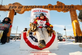 Mitch Seavey poses with his lead dogs Pilot and Crisp on the winner's stand after winning his third Iditarod in record time of 8 days, 3 hours, 40 minutes and 13 seconds in Nome during the 2017 Iditarod on Tuesday afternoon March 14, 2017.Photo by Jeff Schultz/SchultzPhoto.com  (C) 2017  ALL RIGHTS RESERVED