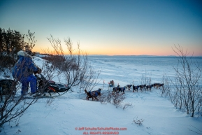Hugh Neff runs down the bank and onto the sea ice of Norton Sound as he leaves the Koyuk checkpoint during the 2017 Iditarod on Tuesday morning March 12, 2017.Photo by Jeff Schultz/SchultzPhoto.com  (C) 2017  ALL RIGHTS RESERVED