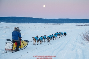 Hans Gatt runs on the sea ice of Norton Sound after leaving the Koyuk checkpoint with a full  moon setting during the 2017 Iditarod on Tuesday morning March 12, 2017.Photo by Jeff Schultz/SchultzPhoto.com  (C) 2017  ALL RIGHTS RESERVED