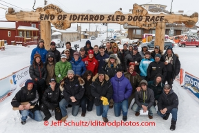 A large portion of the mushers who completed the 2014 Iditarod pose for a photo under the burl arch finish line in Nome on Saturday March 15 during the 2014 Iditarod Sled Dog Race.PHOTO (c) BY JEFF SCHULTZ/IditarodPhotos.com -- REPRODUCTION PROHIBITED WITHOUT PERMISSION
