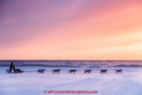 Aaron Burmeister runs on the slough in 30 mph wind leaving the Unalakleet checkpoint at sunset on Sunday  March 15, 2015 during Iditarod 2015.  (C) Jeff Schultz/SchultzPhoto.com - ALL RIGHTS RESERVED DUPLICATION  PROHIBITED  WITHOUT  PERMISSION