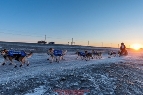 Aliy Zirkle runs on the trail on the Bering Sea shoreline at sunrise just a few miles before the finish  in Nome for a third place finish on Tuesday March 15th during the 2016 Iditarod.  Alaska    Photo by Jeff Schultz (C) 2016  ALL RIGHTS RESERVED
