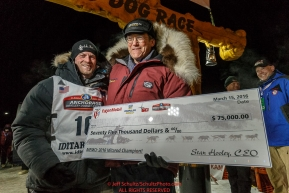 Dallas Seavey is presented with the winning check from Donlin Gold sponsor Stan Foo after winning the 44th running of the Iditarod Sled Dog Race in Nome on Tuesday March 15th during the 2016 Iditarod in record time of 8 Days 11 hours 20 minutes 16 seconds   Photo by Jeff Schultz (C) 2016  ALL RIGHTS RESERVED