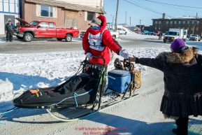 Ryan Redington gives a high-five to a race fan as he runs down Front Street toward the finish line in Nome during the 2017 Iditarod on Wednesday March 15, 2017.Photo by Jeff Schultz/SchultzPhoto.com  (C) 2017  ALL RIGHTS RESERVED