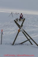 Lisbet Norris on the trail a few miles from the Nome finish line passes tripod trail markers on her way to Nome on Saturday March 15 during the 2014 Iditarod Sled Dog Race.PHOTO (c) BY JEFF SCHULTZ/IditarodPhotos.com -- REPRODUCTION PROHIBITED WITHOUT PERMISSION