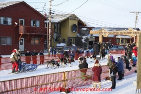 Russian musher Mikhail Telpin runs into the chute on Front Street in Nome to finish the Iditarod Sled Dog Race 2013Photo by Jeff Schultz copyright 2013 DO NOT REPRODUCE WITHOUT PERMISSION