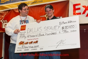 Dallas Seavey gets his winner's check from Scott A. Johnson with Wells Fargo Bank Alaska at the musher 's finishers banquet in Nome on Sunday March 16 after the 2014 Iditarod Sled Dog Race.PHOTO (c) BY JEFF SCHULTZ/IditarodPhotos.com -- REPRODUCTION PROHIBITED WITHOUT PERMISSION