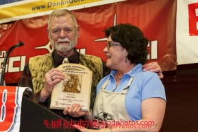 Greg Bill is honored with the Herbie Nayokpuk spirit of the Iditarod award as he retires after his 42 years of working with the Iditarod at the musher 's finishers banquet in Nome.  His wife Annie at his side. Sunday March 16 after the 2014 Iditarod Sled Dog Race.PHOTO (c) BY JEFF SCHULTZ/IditarodPhotos.com -- REPRODUCTION PROHIBITED WITHOUT PERMISSION