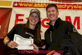 BBNC president Jason Metrokin pressents the Bristol Bay Native Corporation Fish First Award to Aliy Zirkle at the musher 's finishers banquet in Nome on Sunday March 16 after the 2014 Iditarod Sled Dog Race.PHOTO (c) BY JEFF SCHULTZ/IditarodPhotos.com -- REPRODUCTION PROHIBITED WITHOUT PERMISSION