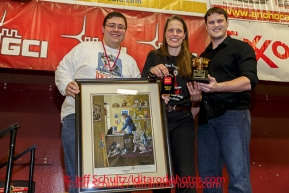 Jake Slingsby and Scott A. Johnsn present Aliy Zirkle with teh Wells Fargo Bank Alaska Gold Coast Award at the musher 's finishers banquet in Nome on Sunday March 16 after the 2014 Iditarod Sled Dog Race.PHOTO (c) BY JEFF SCHULTZ/IditarodPhotos.com -- REPRODUCTION PROHIBITED WITHOUT PERMISSION