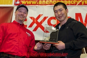 Aaron Burmeister presents the Sportsmanship Award to Mike Williams Jr. at the musher 's finishers banquet in Nome on Sunday March 16 after the 2014 Iditarod Sled Dog Race.PHOTO (c) BY JEFF SCHULTZ/IditarodPhotos.com -- REPRODUCTION PROHIBITED WITHOUT PERMISSION