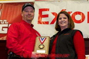 ExxonMobil representative Karen Hagedorn presents Aaron Burmeister with the ExxonMobil Musher's Choice Award at the musher 's finishers banquet in Nome on Sunday March 16 after the 2014 Iditarod Sled Dog Race.PHOTO (c) BY JEFF SCHULTZ/IditarodPhotos.com -- REPRODUCTION PROHIBITED WITHOUT PERMISSION