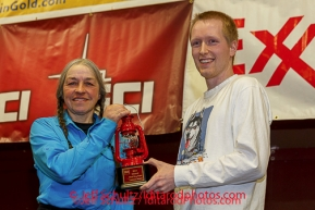 Wells Fargo, Tyler Hull, presents Marcelle Fresineau with the Red Lantern Award at the musher 's finishers banquet in Nome on Sunday March 16 after the 2014 Iditarod Sled Dog Race.PHOTO (c) BY JEFF SCHULTZ/IditarodPhotos.com -- REPRODUCTION PROHIBITED WITHOUT PERMISSION