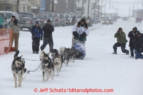Christine Roalofs runs on Front Street and into the finish chute in Nome to finish in last place and be the winner of the Red Lantern Award   Iditarod Sled Dog Race 2013Photo by Jeff Schultz copyright 2013 DO NOT REPRODUCE WITHOUT PERMISSION