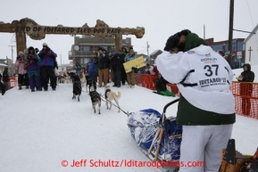 Christine Roalofs runs into the chute and across the finish line to finish in last place and is the winner of the Red Lantern Award on Front Street in Nome.  Iditarod Sled Dog Race 2013Photo by Jeff Schultz copyright 2013 DO NOT REPRODUCE WITHOUT PERMISSION