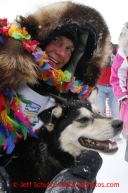 Christine Roalofs who finished in last place and winner of the Red Lantern Award gives her lead dog a big hug on Front Street in Nome.  Iditarod Sled Dog Race 2013Photo by Jeff Schultz copyright 2013 DO NOT REPRODUCE WITHOUT PERMISSION