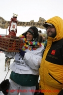 Christine Roalofs, who finished in last place and is winner of the Red Lantern Award, is presented the award by race sponsor representative Scott A Johnson of Wells Fargo at the finish line on Front Street in Nome.  Iditarod Sled Dog Race 2013Photo by Jeff Schultz copyright 2013 DO NOT REPRODUCE WITHOUT PERMISSION