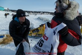 Dallas Seavey recieves his race bib from checker Beverly Andersson just before leaving the White Mountain checkpoint on Tuesday March 16, 2015 during Iditarod 2015.  (C) Jeff Schultz/SchultzPhoto.com - ALL RIGHTS RESERVED DUPLICATION  PROHIBITED  WITHOUT  PERMISSION