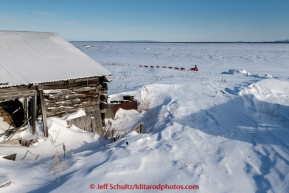 DeeDee Jonrowe runs past abandoned buildings of Old Shaktoolik, a few miles before the Shaktoolik checkpoint on Tuesday March 16, 2015 during Iditarod 2015.  (C) Jeff Schultz/SchultzPhoto.com - ALL RIGHTS RESERVED DUPLICATION  PROHIBITED  WITHOUT  PERMISSION