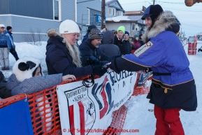 Ken Anderson's wife Gwenn hands out dog booties shorlty after Ken finished at the Nome finish line on Wednesday March 18, 2015 during Iditarod 2015.  (C) Jeff Schultz/SchultzPhoto.com - ALL RIGHTS RESERVED DUPLICATION  PROHIBITED  WITHOUT  PERMISSION