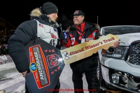 Dallas Seavey recieves the key to his new Dodge Truck from Anchorage Chrysler Dodge sponsor rep Chuck Talskey after winning his 3rd Iditarod in 8 days 18 hours 13 minutes 6 seconds on Wednesday March 18, 2015 during Iditarod 2015.  (C) Jeff Schultz/SchultzPhoto.com - ALL RIGHTS RESERVED DUPLICATION  PROHIBITED  WITHOUT  PERMISSION