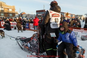 Aaron Burmeister's son Hunter rides on the sled caboose as Aaron runs his team to the dog lot after finishing in third place at the Nome finish line on Wednesday March 18, 2015 during Iditarod 2015.  (C) Jeff Schultz/SchultzPhoto.com - ALL RIGHTS RESERVED DUPLICATION  PROHIBITED  WITHOUT  PERMISSION