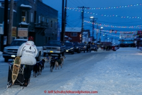 Martin Buser runs down Front Street on his way toward the finish line in Nome on Thursday March 19, 2015 during Iditarod 2015.  (C) Jeff Schultz/SchultzPhoto.com - ALL RIGHTS RESERVED DUPLICATION  PROHIBITED  WITHOUT  PERMISSION