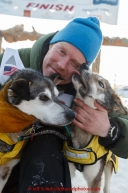 Mats Pettersson hugs his leaders at the finish line in Nome on Thursday March 19, 2015 during Iditarod 2015.  (C) Jeff Schultz/SchultzPhoto.com - ALL RIGHTS RESERVED DUPLICATION  PROHIBITED  WITHOUT  PERMISSION