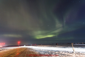 Northern Lights peek through the cloud layer as Michelle Phillips headlamp shines as moves toward the finish line in Nome on Thursday March 19, 2015 during Iditarod 2015.  (C) Jeff Schultz/SchultzPhoto.com - ALL RIGHTS RESERVED DUPLICATION  PROHIBITED  WITHOUT  PERMISSION