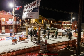 Michelle Phillips checks in after finishing her race under the burl arch finish line in Nome on Thursday March 19, 2015 during Iditarod 2015.  (C) Jeff Schultz/SchultzPhoto.com - ALL RIGHTS RESERVED DUPLICATION  PROHIBITED  WITHOUT  PERMISSION