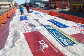 Sponsor banners are taken down and rolled up at the Nome finish line during the 2016 Iditarod.  Alaska      Photo by Jeff Schultz (C) 2016  ALL RIGHTS RESERVED
