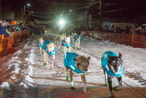 Mary Helwig runs into the Nome finish line as she finishes last to claim the red lantern award and was the one to extinquish the Widow's lamp during the 2016 Iditarod.  Alaska      Photo by Jeff Schultz (C) 2016  ALL RIGHTS RESERVED