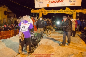 Mary Helwig at the Nome finish line finishes last to claim the red lantern award and was the one to extinquish the Widow's lamp during the 2016 Iditarod.  Alaska      Photo by Jeff Schultz (C) 2016  ALL RIGHTS RESERVED
