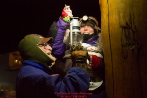 Mary Helwig at the Nome finish line extinquishes the Widow's lamp with the help of Leo Rasmusson after she finished  the 2016 Iditarod.  Alaska      Photo by Jeff Schultz (C) 2016  ALL RIGHTS RESERVED