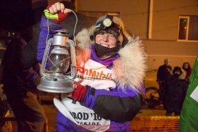 Mary Helwig at the Nome finish line holds up the Widow's lamp during the 2016 Iditarod.  Alaska      Photo by Jeff Schultz (C) 2016  ALL RIGHTS RESERVED