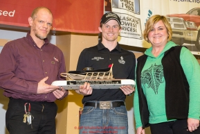 The GCI Dorothy G. Page Halfway Award is presented by Heather Handyside, director of communications for GCI  to Dallas Seavey at the musher finisher's banquet in Nome during the 2016 Iditarod.  Alaska      Photo by Jeff Schultz (C) 2016  ALL RIGHTS RESERVED