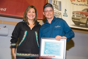 The Bristol Bay Native Corporation Fish First Award is presented by Andria Agli, vice president, shareholder and corporate relations for Bristol Bay Native Corporation to Mitch Seavey at the musher finisher's banquet in Nome during the 2016 Iditarod.  Alaska      Photo by Jeff Schultz (C) 2016  ALL RIGHTS RESERVED