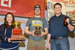 The Wells Fargo Gold Coast Award is presented by Jake Slingsby, vice president & senior business relations manager for Wells Fargo, and Callie King, operations supervisor for the Nome Wells Fargo branch to Brent Sass at the musher finisher's banquet in Nome during the 2016 Iditarod.  Alaska      Photo by Jeff Schultz (C) 2016  ALL RIGHTS RESERVED
