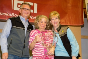 DeeDee Jonrowe is re-presented a replica of the 1991 Alaska Airlines Leonhard Seppala award after it was lost in the Sockeye Fire by Marilyn Romano, regional vice president,  and Tim Thompson, manager, external affairs, with Alaska Airlinesat the musher finisher's banquet in Nome during the 2016 Iditarod.  Alaska      Photo by Jeff Schultz (C) 2016  ALL RIGHTS RESERVED