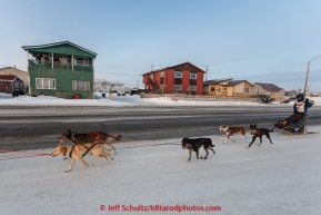 Becca Moore runs down Front Street as residents cheer her on a mile or so from the finsih line in Nome on Saturday March 21, 2015 during Iditarod 2015.  (C) Jeff Schultz/SchultzPhoto.com - ALL RIGHTS RESERVED DUPLICATION  PROHIBITED  WITHOUT  PERMISSION