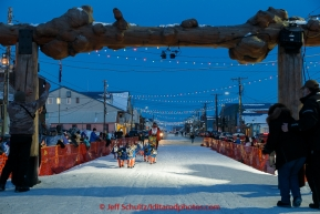Alan Eischens runs into the finish chute and under the burl arch in Nome on Saturday March 21, 2015 during Iditarod 2015.  (C) Jeff Schultz/SchultzPhoto.com - ALL RIGHTS RESERVED DUPLICATION  PROHIBITED  WITHOUT  PERMISSION