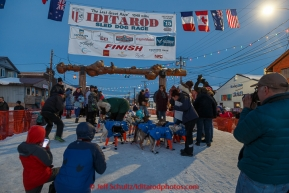A crowd gathers around Alan Eischens in the finish chute in Nome shortly afer he arrived on Saturday March 21, 2015 during Iditarod 2015.  (C) Jeff Schultz/SchultzPhoto.com - ALL RIGHTS RESERVED DUPLICATION  PROHIBITED  WITHOUT  PERMISSION