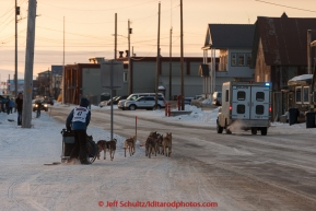 Becca Moore runs on Front Street with a police escort just a mile from the finish line in Nome on Saturday March 21, 2015 during Iditarod 2015.  (C) Jeff Schultz/SchultzPhoto.com - ALL RIGHTS RESERVED DUPLICATION  PROHIBITED  WITHOUT  PERMISSION