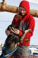Rohn Buser plays with Berretta, one of the dogs run to Nome by Alan Stevens at the finish line in Nome on Saturday March 21, 2015 during Iditarod 2015.  (C) Jeff Schultz/SchultzPhoto.com - ALL RIGHTS RESERVED DUPLICATION  PROHIBITED  WITHOUT  PERMISSION