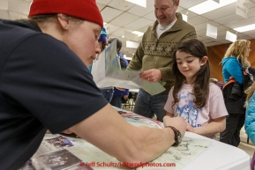 Aliy Zirkle signs an autograph for a youngster as all the mushers who've finished the race as of Saturday March 21st are on hand at the Nome Mini-Convention Center to sign autographs for race fans during Iditarod 2015.  (C) Jeff Schultz/SchultzPhoto.com - ALL RIGHTS RESERVED DUPLICATION  PROHIBITED  WITHOUT  PERMISSION
