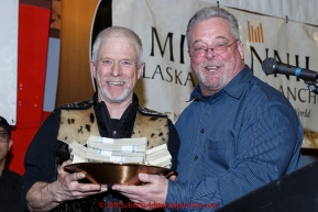 Jeff King (L) recieves the Millenium Hotel 1st musher to the Yukon award from Patrick Cashman at the finishers banquet in Nome on Sunday  March 22, 2015 during Iditarod 2015.  (C) Jeff Schultz/SchultzPhoto.com - ALL RIGHTS RESERVED DUPLICATION  PROHIBITED  WITHOUT  PERMISSION