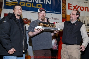 Aaron Burmeister (center) recieves the GCI Dorothy G. Page Halfway award from Dave Fancott and Greg Menendez of GCI at the finishers banquet in Nome on Sunday  March 22, 2015 during Iditarod 2015.  (C) Jeff Schultz/SchultzPhoto.com - ALL RIGHTS RESERVED DUPLICATION  PROHIBITED  WITHOUT  PERMISSION