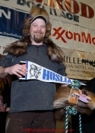 Aaron Burmeister shows off his native-made gifts from the villagers of Huslia for being the first musher to their half-way checkpoint at the finishers banquet in Nome on Sunday  March 22, 2015 during Iditarod 2015.  (C) Jeff Schultz/SchultzPhoto.com - ALL RIGHTS RESERVED DUPLICATION  PROHIBITED  WITHOUT  PERMISSION