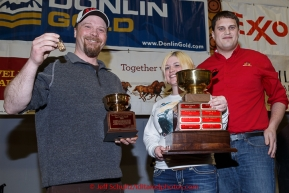 Aaron Burmeister recieves the Wells Fargo Bank Gold Coast award from Jake Slingsby and Jessica Osgood at the finishers banquet in Nome on Sunday  March 22, 2015 during Iditarod 2015.  (C) Jeff Schultz/SchultzPhoto.com - ALL RIGHTS RESERVED DUPLICATION  PROHIBITED  WITHOUT  PERMISSION