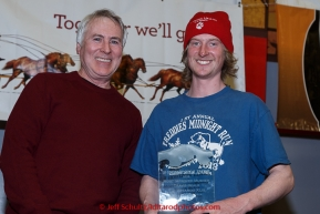 Travis Beals (R)  recieves the Horizon Lines Most Improved musher award from John Schweiken at the finishers banquet in Nome on Sunday  March 22, 2015 during Iditarod 2015.  (C) Jeff Schultz/SchultzPhoto.com - ALL RIGHTS RESERVED DUPLICATION  PROHIBITED  WITHOUT  PERMISSION